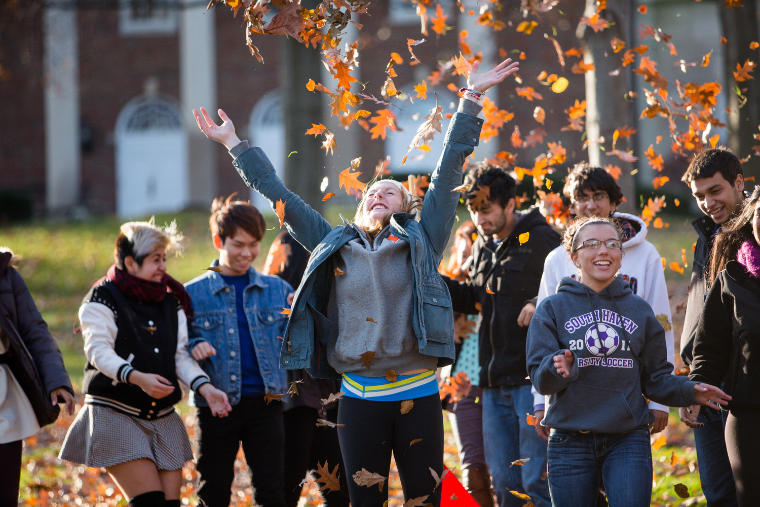 students throwing fall leaves on campus