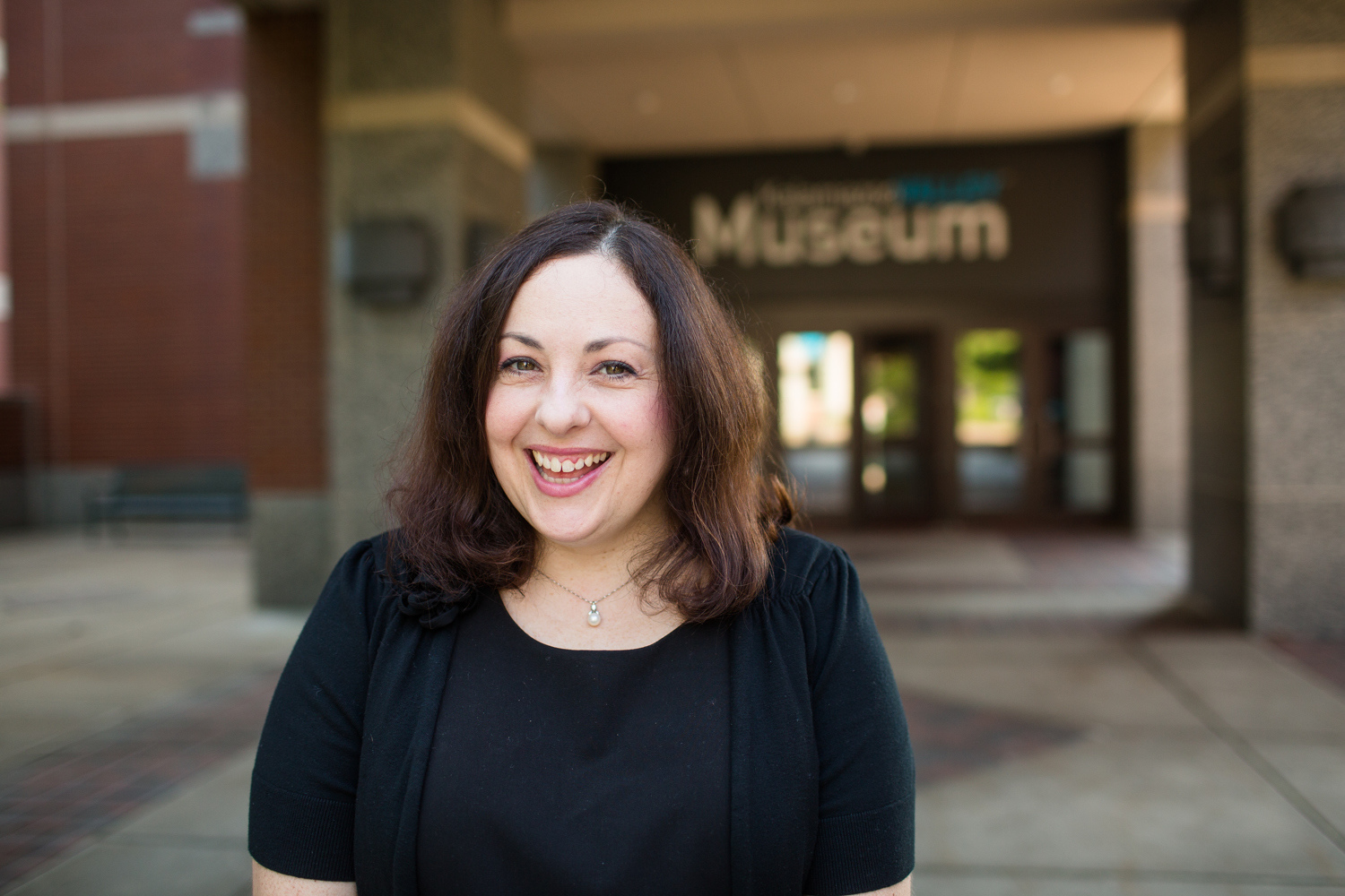 woman posing in front of museum magazine feature