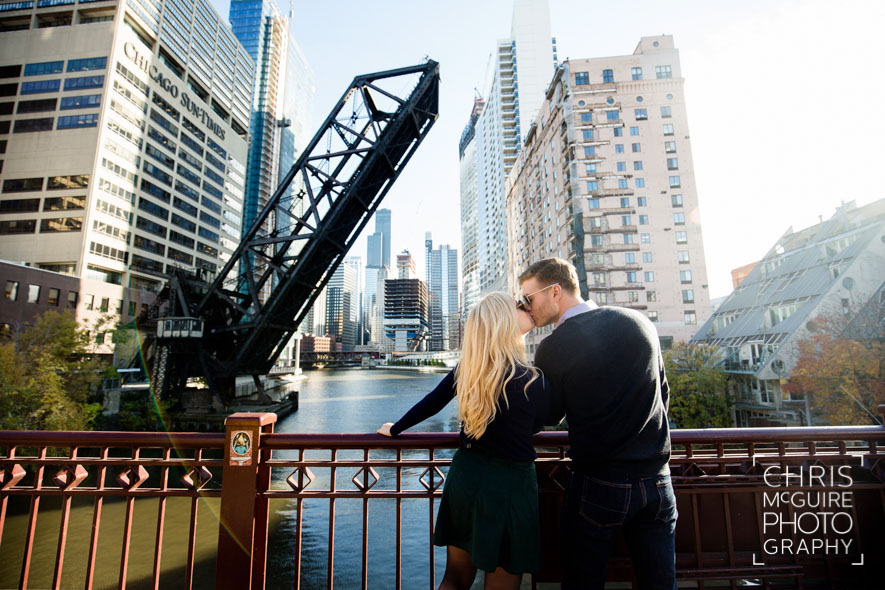 engaged couple kissing with chicago bridge and skyline