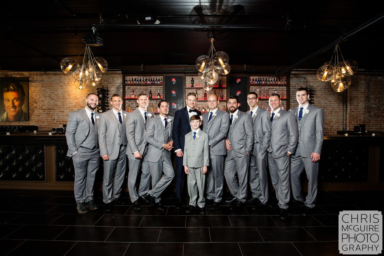 groom and groomsmen posing in bar
