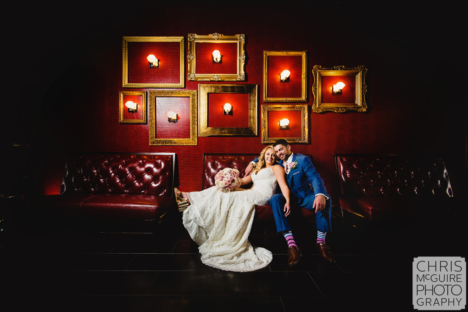 bride and groom with red wall