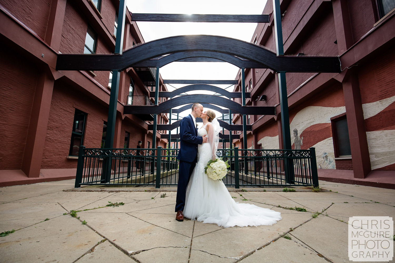 bride groom kiss outside under arches