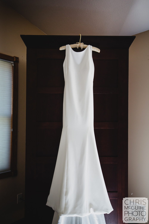 wedding dress hanging on bureau