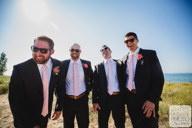 groomsmen laughing by lake