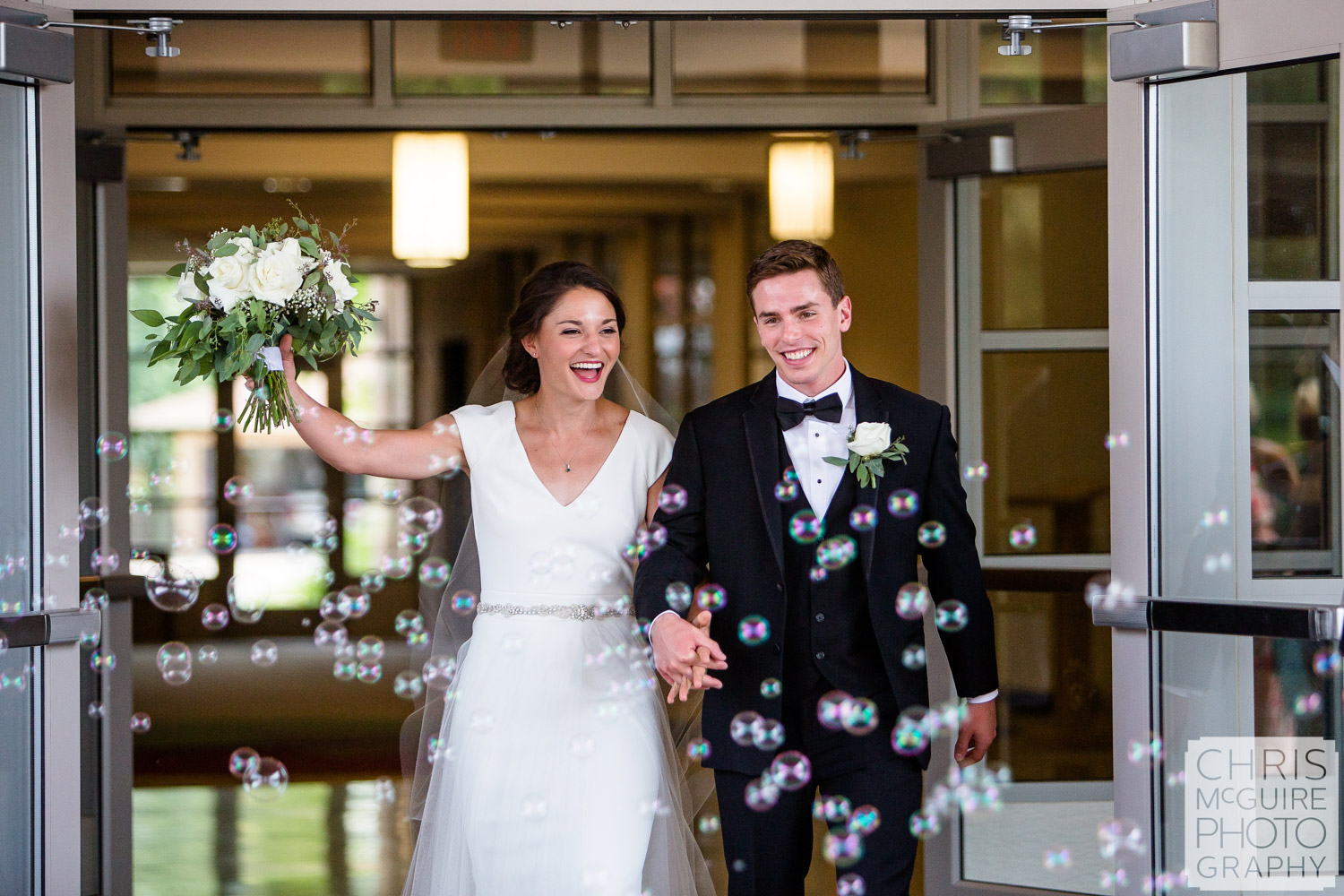 bride and groom walk through bubbles after wedding Blessed Sacrament Morton
