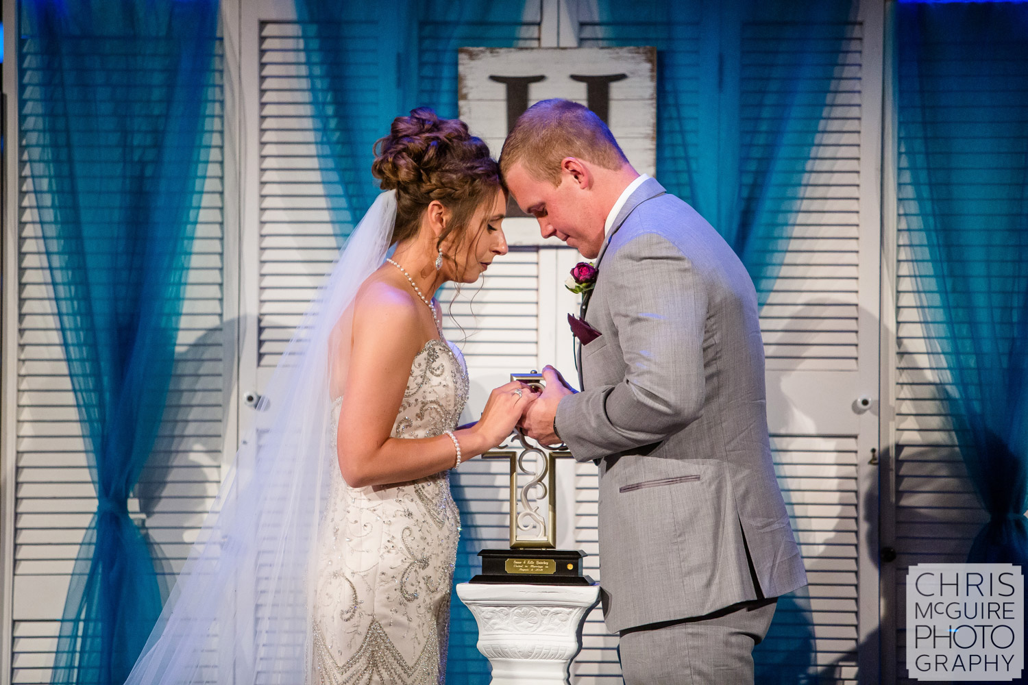 bride and groom pray together at Harvest Bible Chapel Peoria IL Wedding