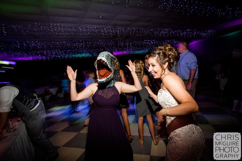 dinosaur mask and bride dancing at wedding reception
