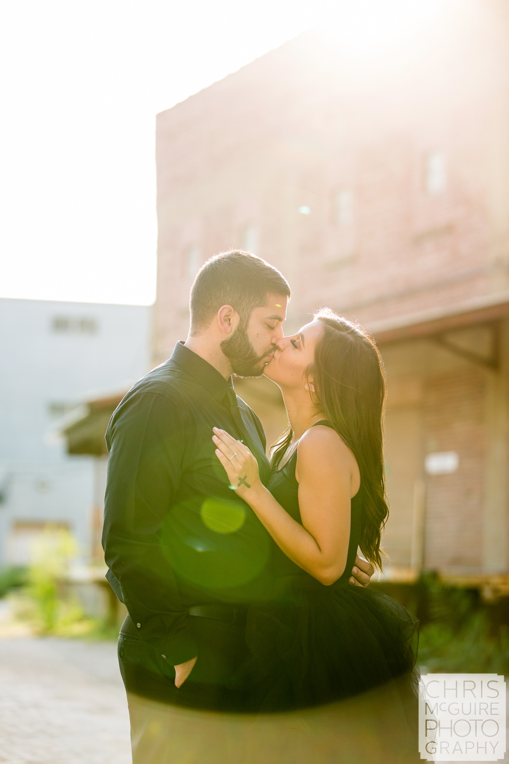 couple kisses in Peoria Warehouse District with solar flare