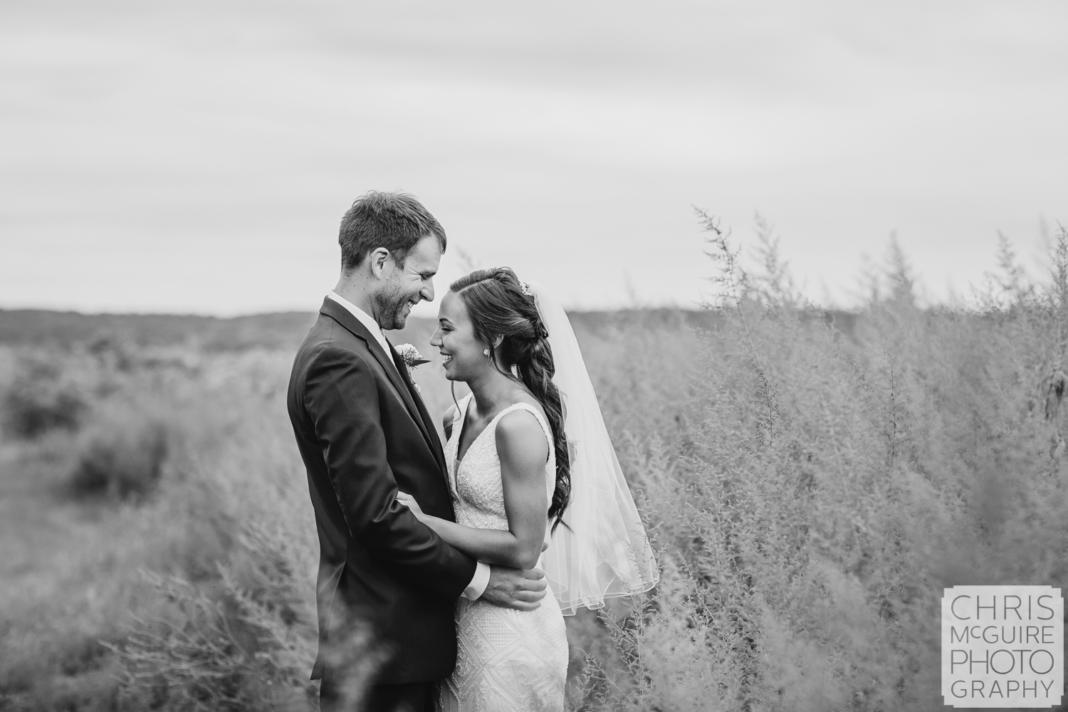 Bride and groom laugh in grass