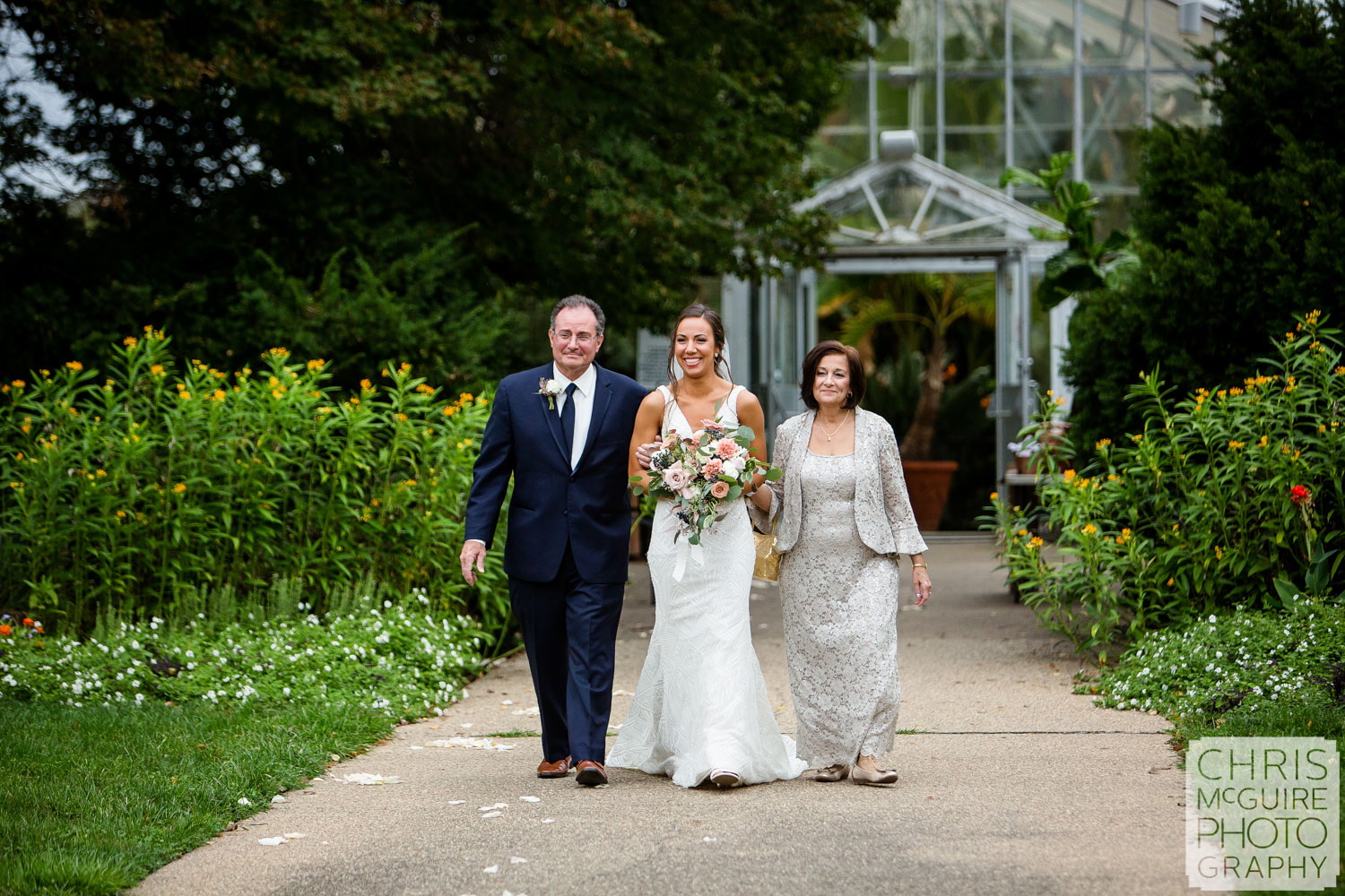 Bride walks down aisle with parents at Luthy