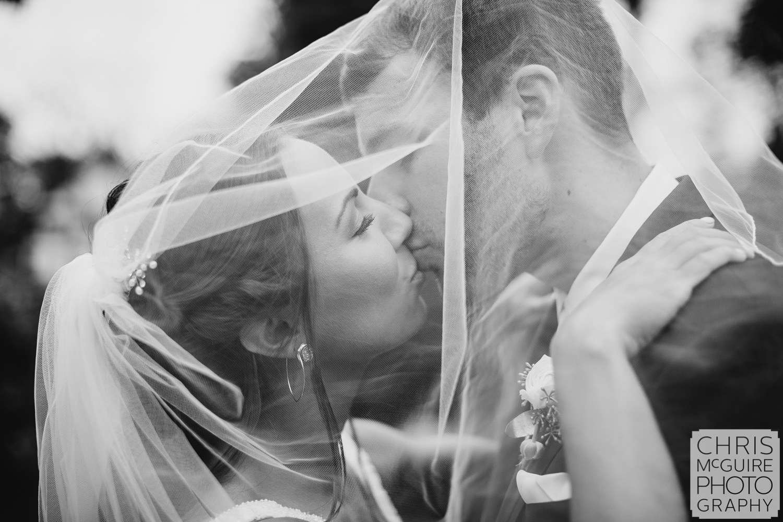 Bride and groom kiss under veil