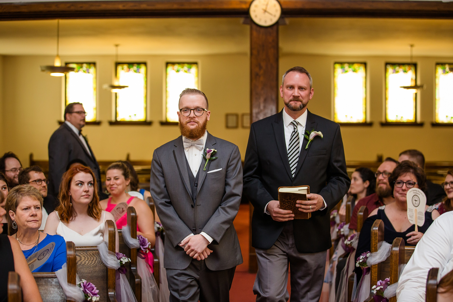 Groom and pastor walk down aisle