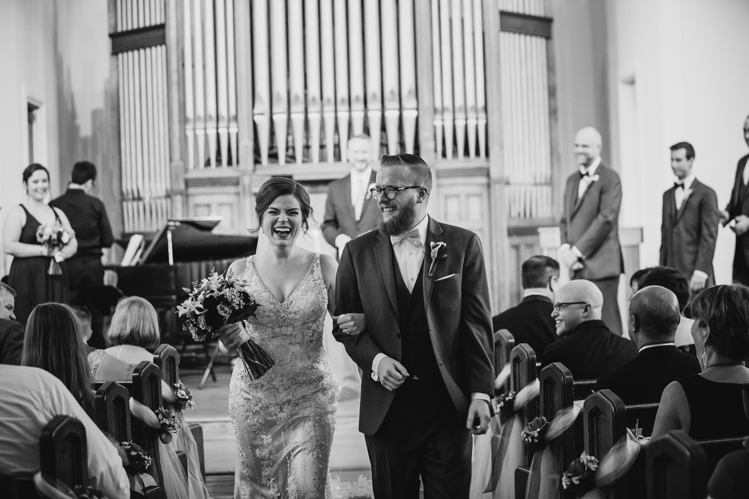 Newlyweds smile as they walk down aisle