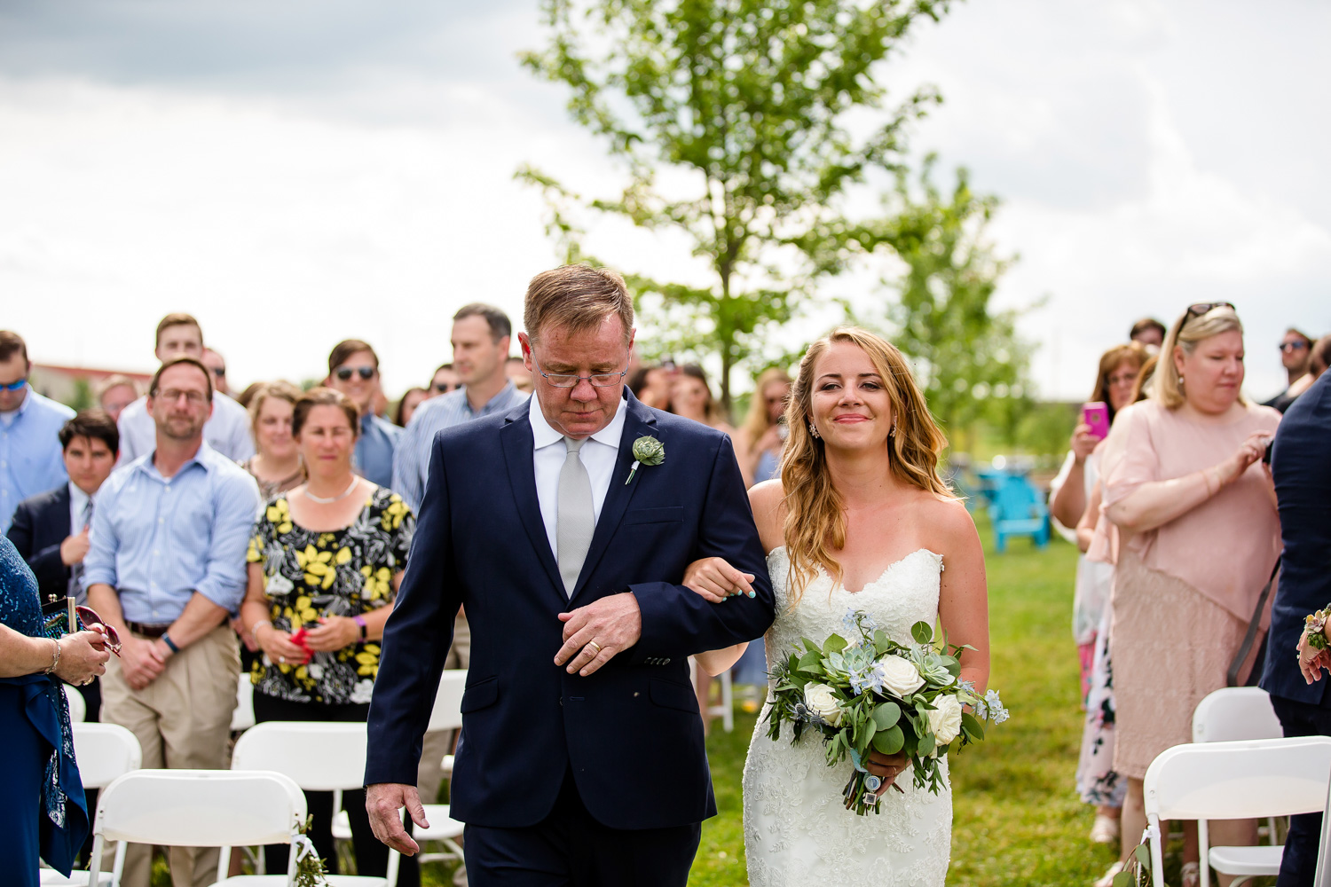 Father walks bride down aisle at outdoor wedding ceremony