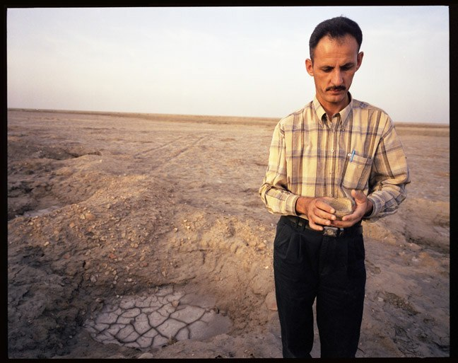 Abdul Amir Hamdani inspecting potery shard at looted archaeological site. May, 2004.