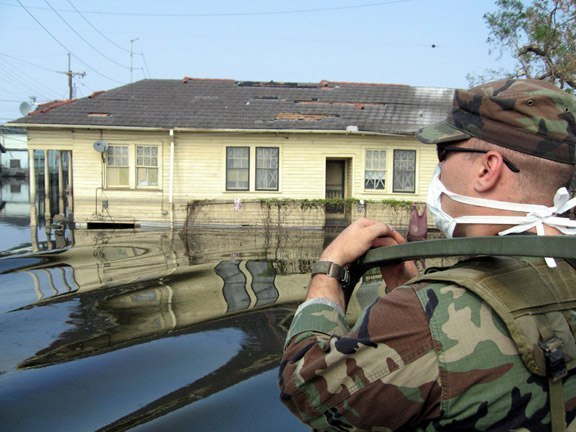 National Guard patrol flooded neighborhood in New Orleans. The National Guard wore face masks to protect against the stench from the fetid, toxic water.