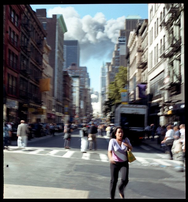 Woman on Broadway runs from the collapse of the first tower in lower Manhattan, September 11, 2001.