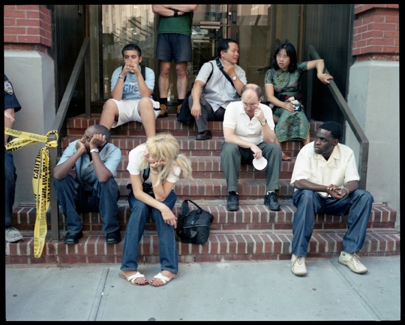 People sitting on stoop in lower Manhattan after the collapse of the two World Trade Center buildings, September 11, 2001.