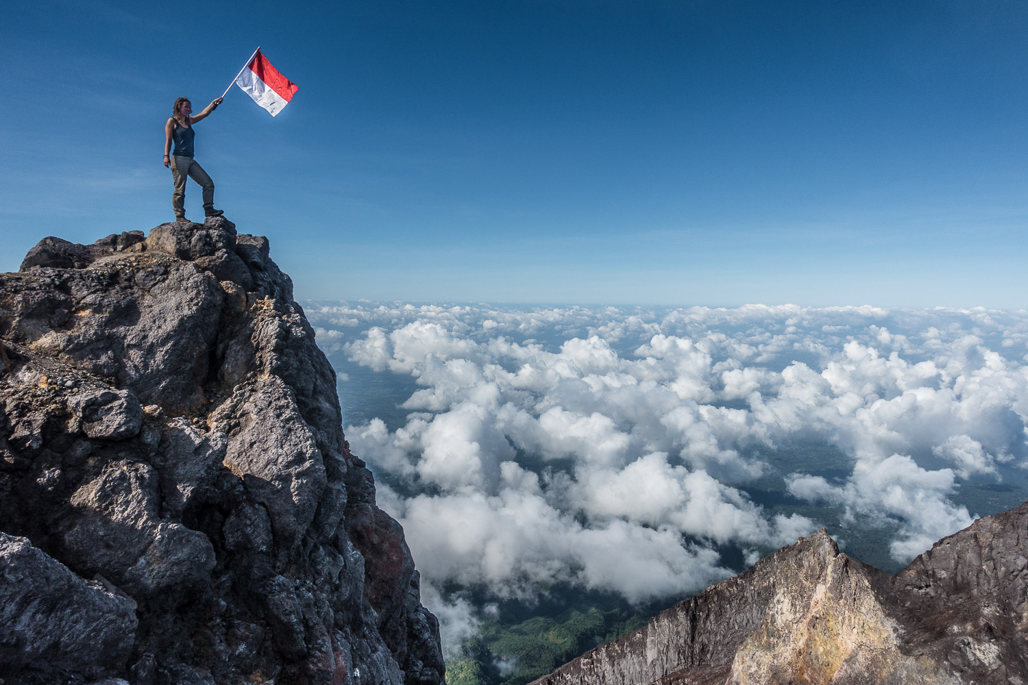 Eva waving the Indonesian flag on the summit of Merapi