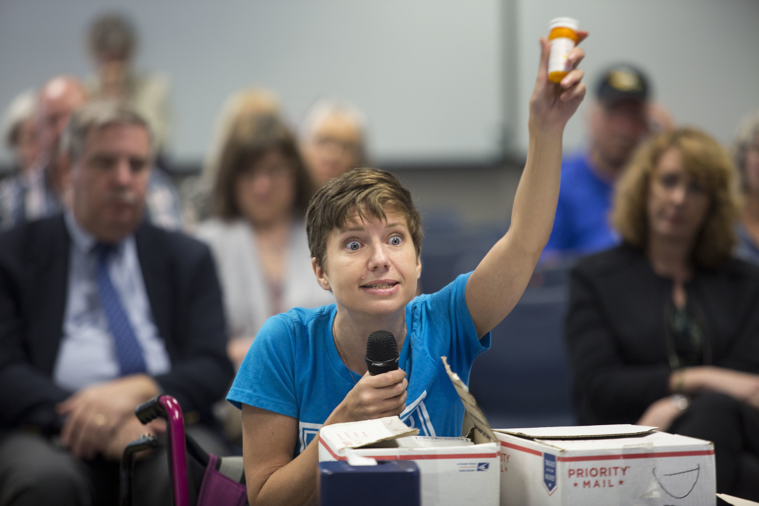 Amanda Siebe holds up her bottle of methadone as she speaks at a hearing to discuss the future availability of opioids under Oregon Medicaid rules in Wilsonville, Oregon August 9, 2018.