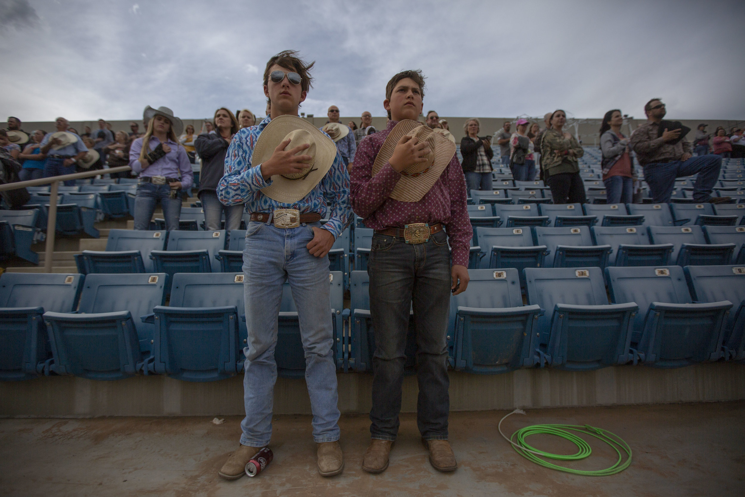 Teenage men hold their cowboy hats over their hearts as they listen to the national anthem at the Utah High School Rodeo Association Finals in Heber City Utah, June 7, 2019.