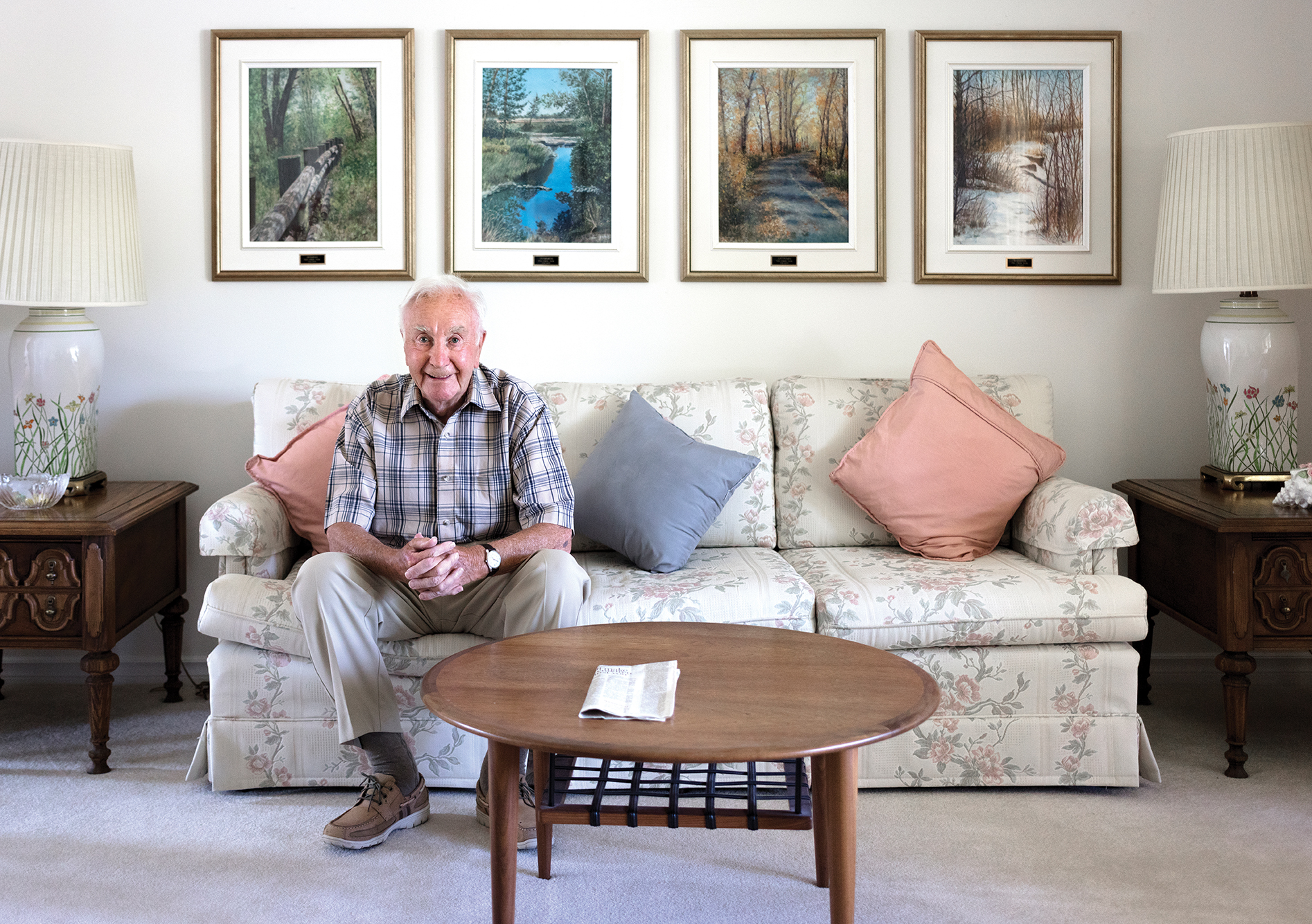 Brian Taylor, who is also an accomplished artist, in his Calgary living room. On the wall behind him are four of his paintings of Fish Creek Park. Photo by Erin Brooke Burns