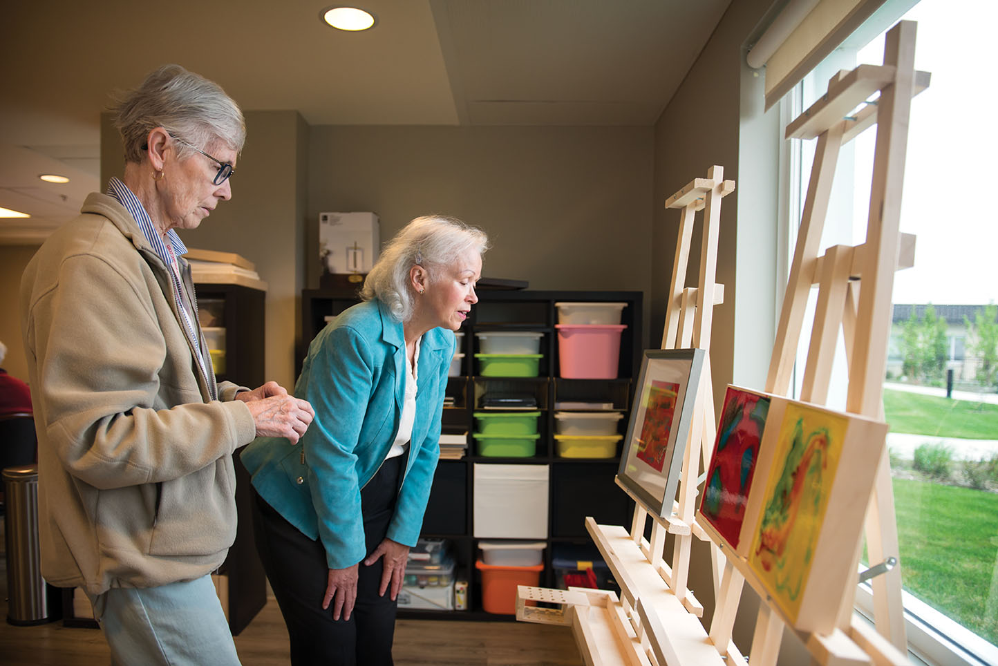 OMA participant Cathy Sherwood, left, and her sister Barb Schultz discuss the art on display at Club 36.
