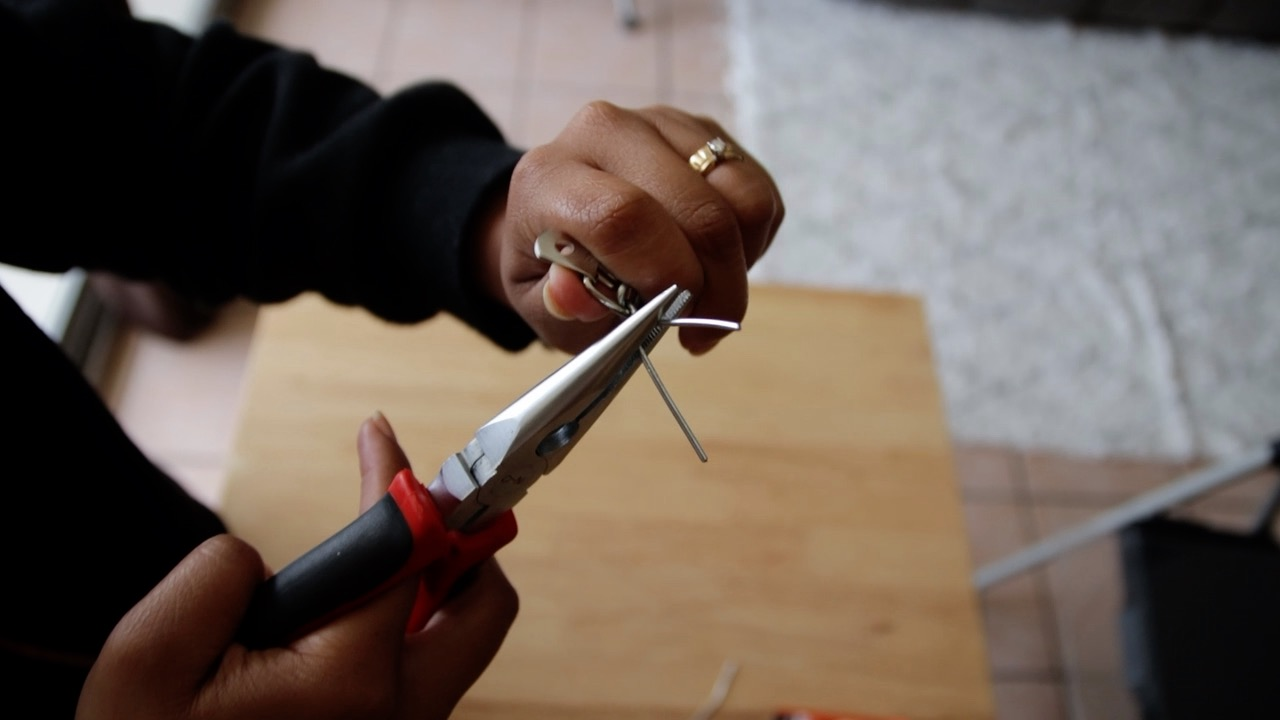Use the pliers to twist the wire and essentially tie the D-ring to the end of the chain. Cut off any excess wire.