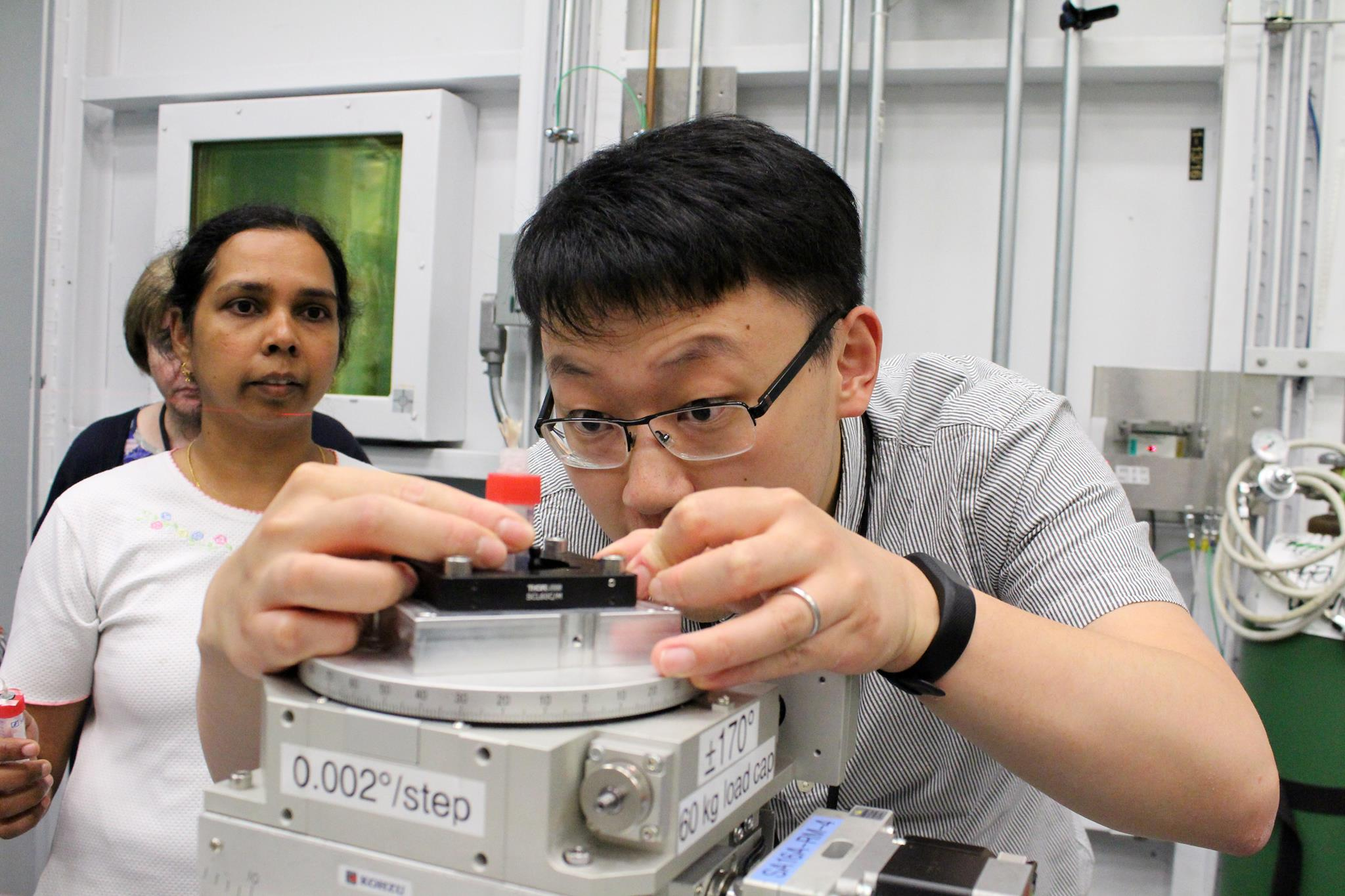 Teng Zhang loads a sample into the beamline for analysis. The flowers his group is studying, members of the Aster family, look like individual flowers, but contain tightly packed assemblies of many small flowers with complex connective tissues.