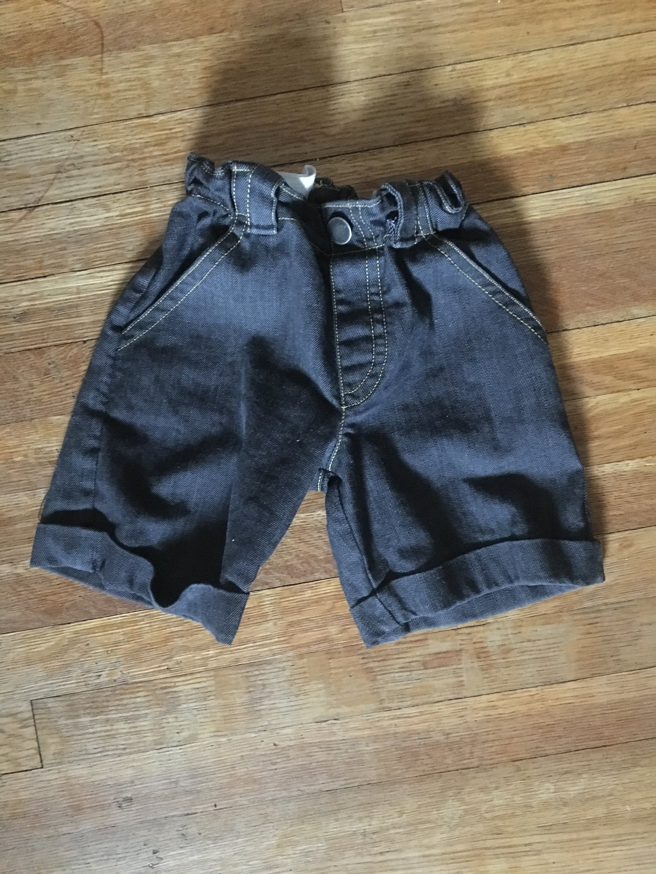 finished jeans shorts cinched to fit child now (visibly pulled in)