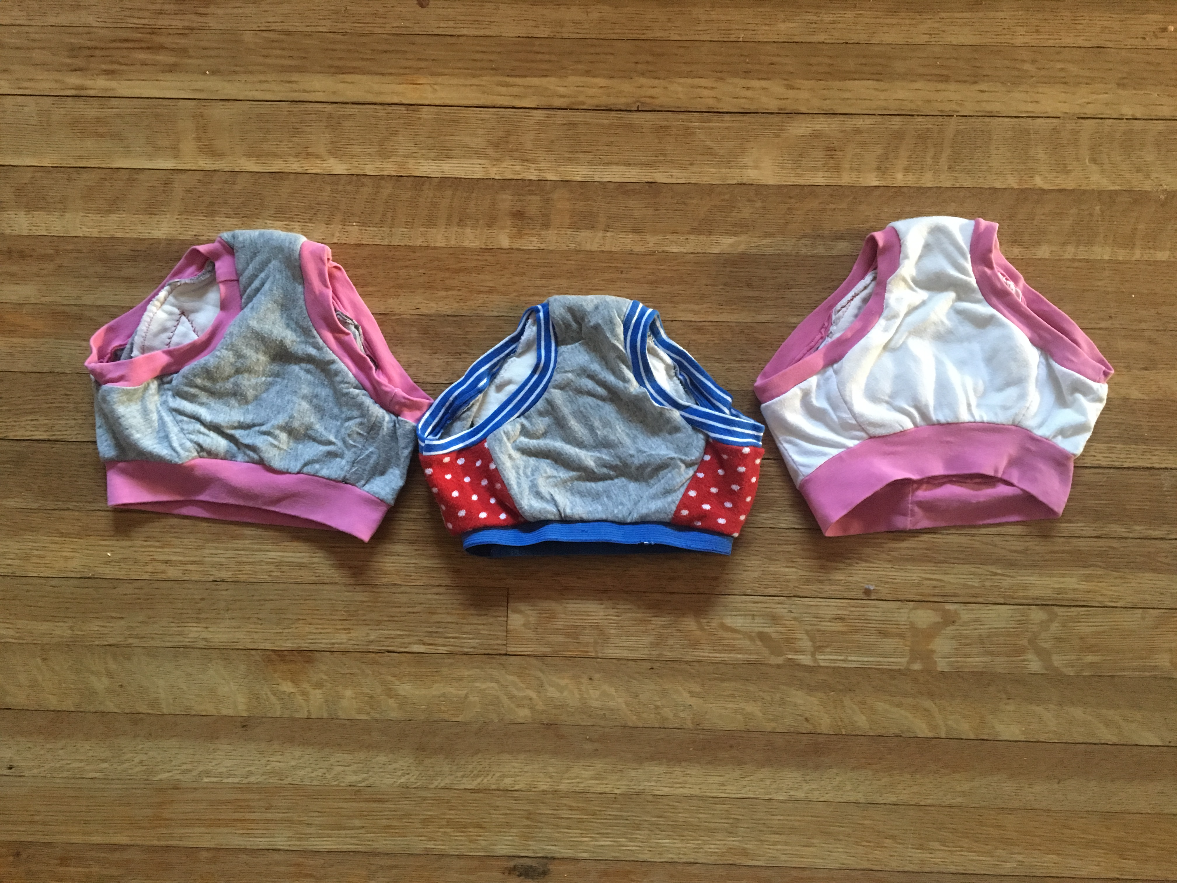 three pairs of toddler underwear, fronts : white with pink bands, grey with blue elastic/bands and red polka dot sides, grey with pink bands