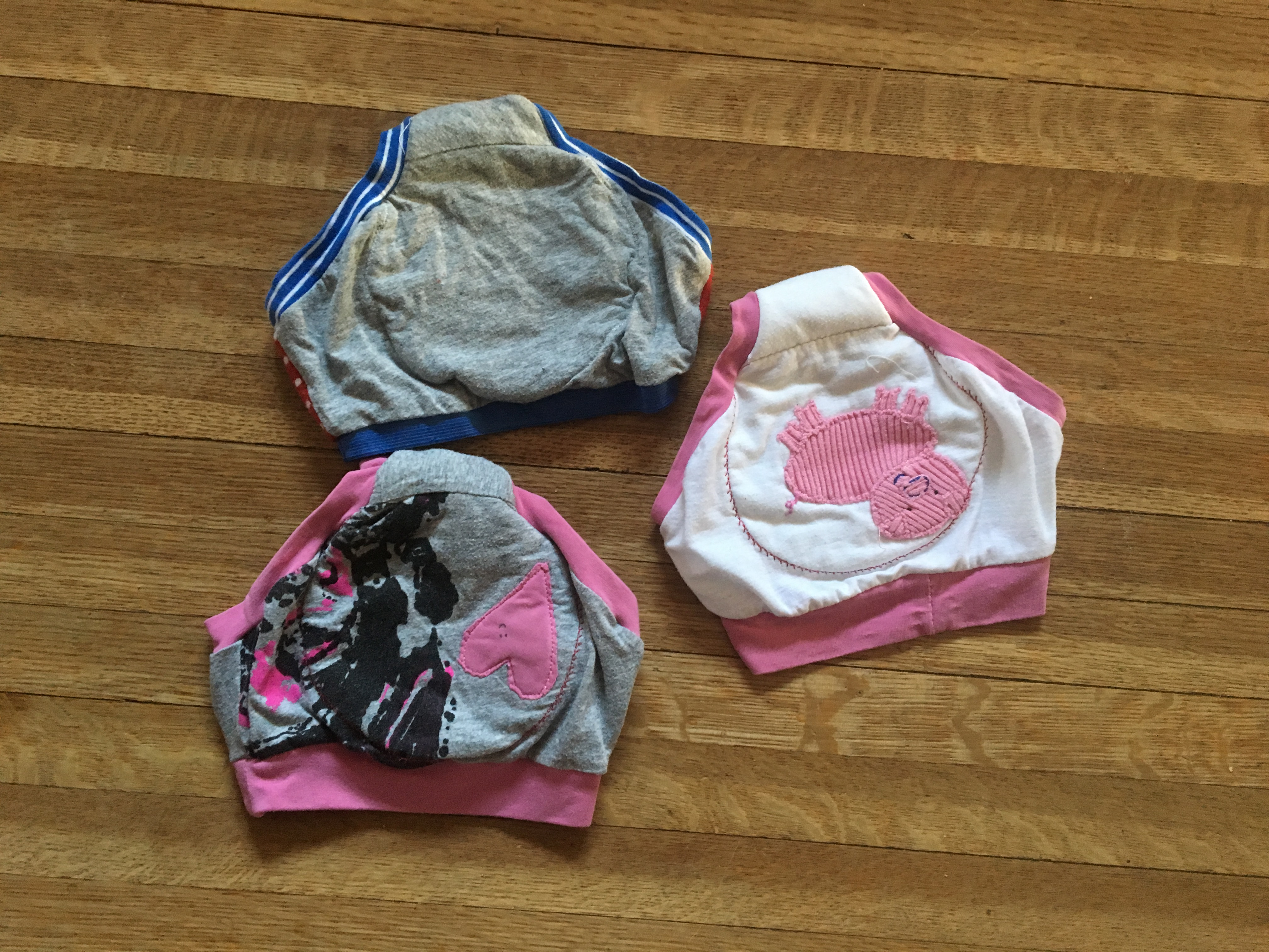 three pairs of toddler underwear: white with pink pig, grey with blue bands, and grey with pink heart