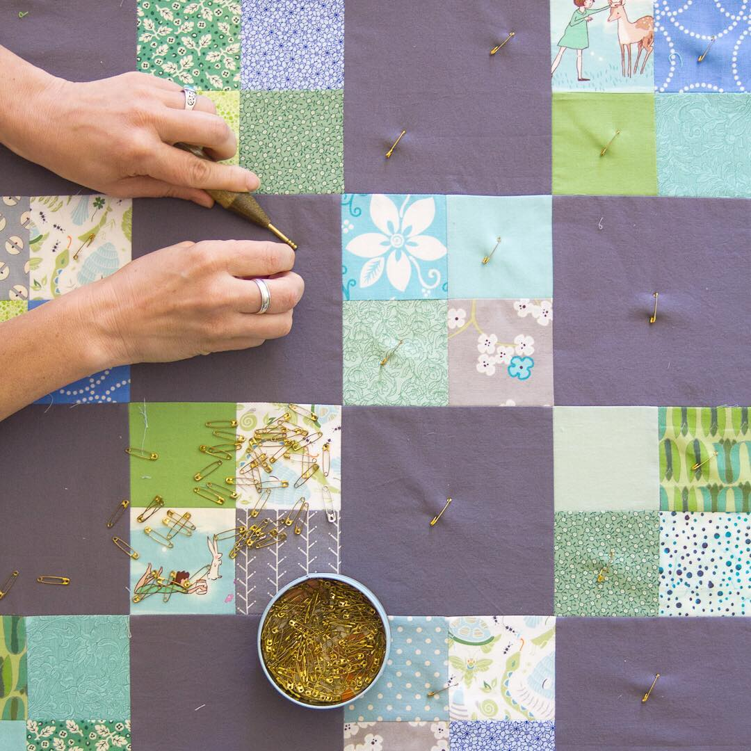 Angela from Hello, Quilting pinning a woodland-themed baby quilt.