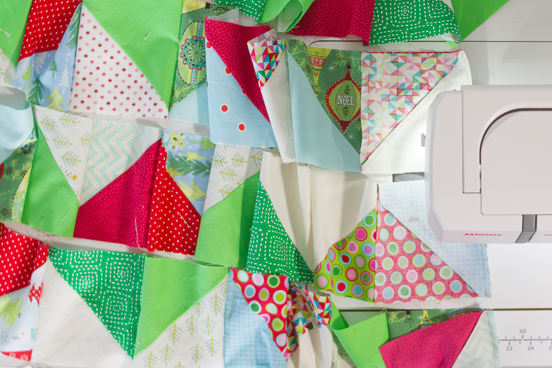 Scrappy Christmas Triangles Quilt Assembly via www.helloquilting.com