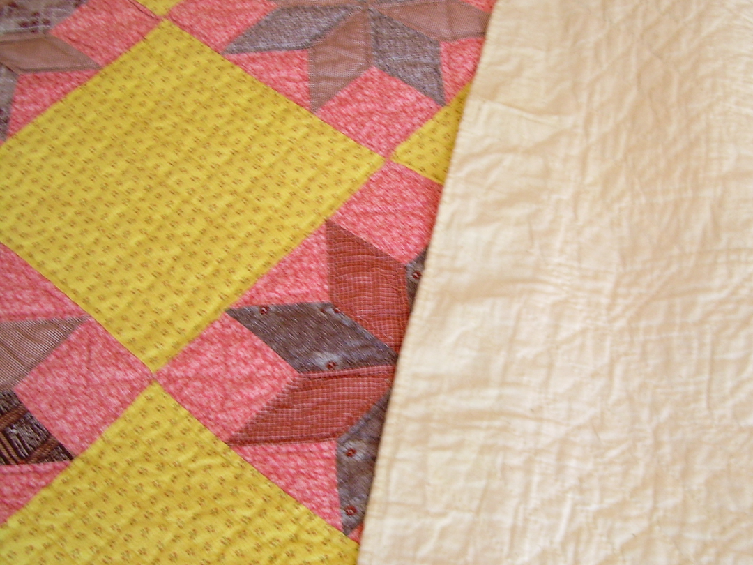 Muslin Backing and Binding on Chrome Yellow and Double Pink Quilt via www.helloquilting.com