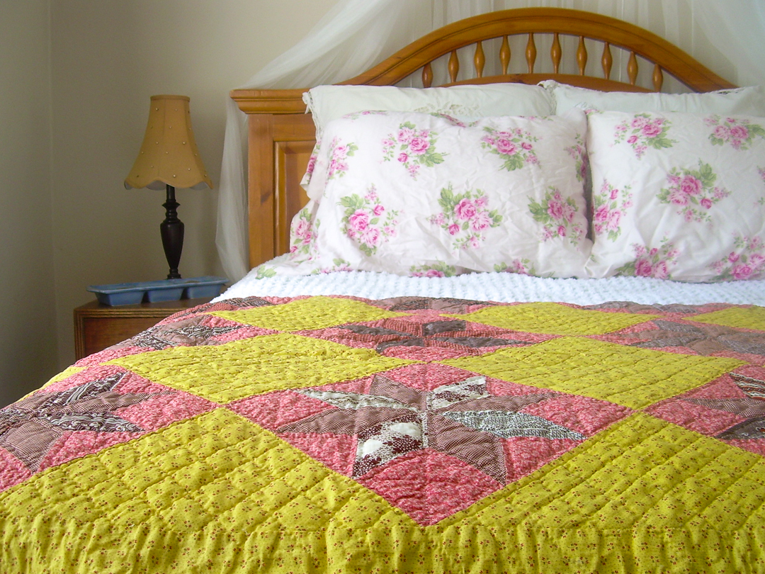 Antique Chrome Yellow and Double Pink Quilt on Wooden Bed via www.helloquilting.com