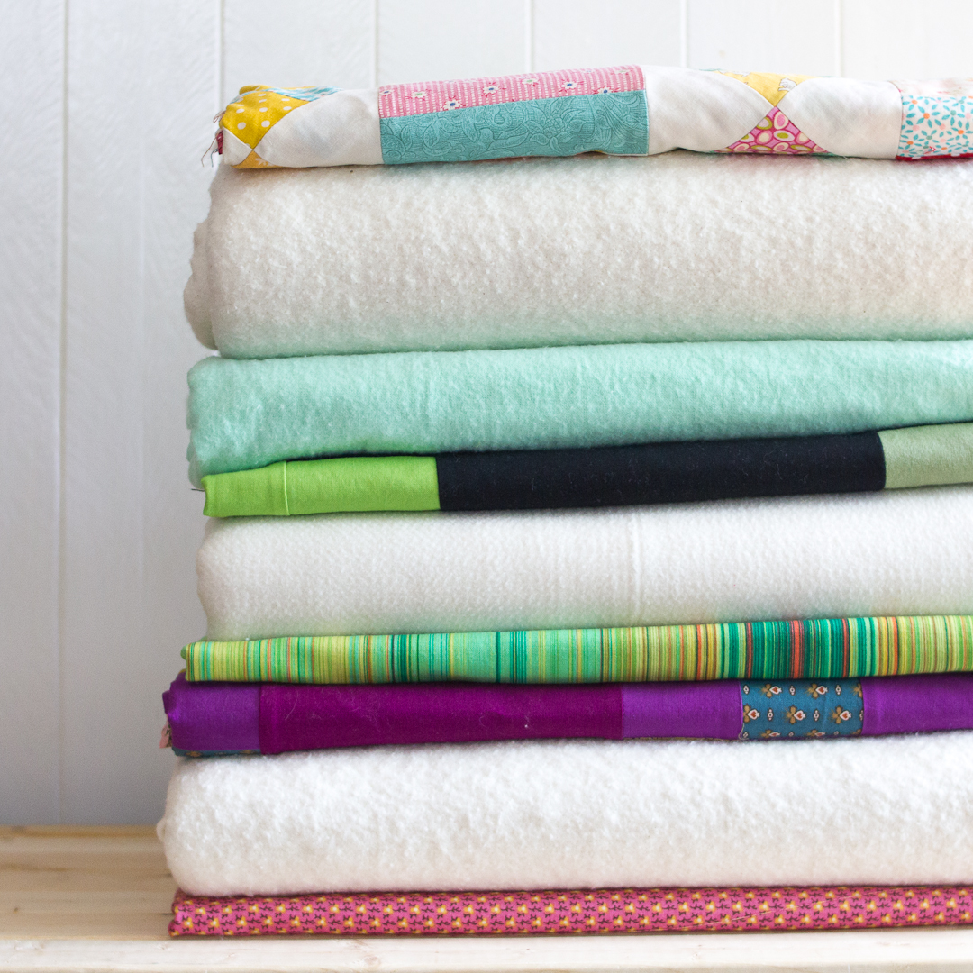 Stack of Quilts Waiting to be Pinned via www.helloquilting.com