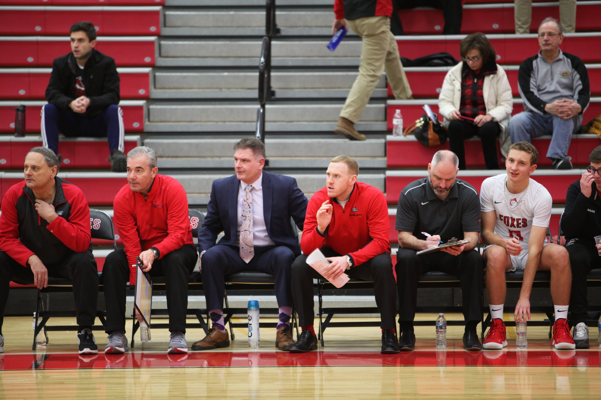 Gabe Skrinjar (second from right) tallies stats as the other members of the coaching staff remain engaged in the game in other ways.