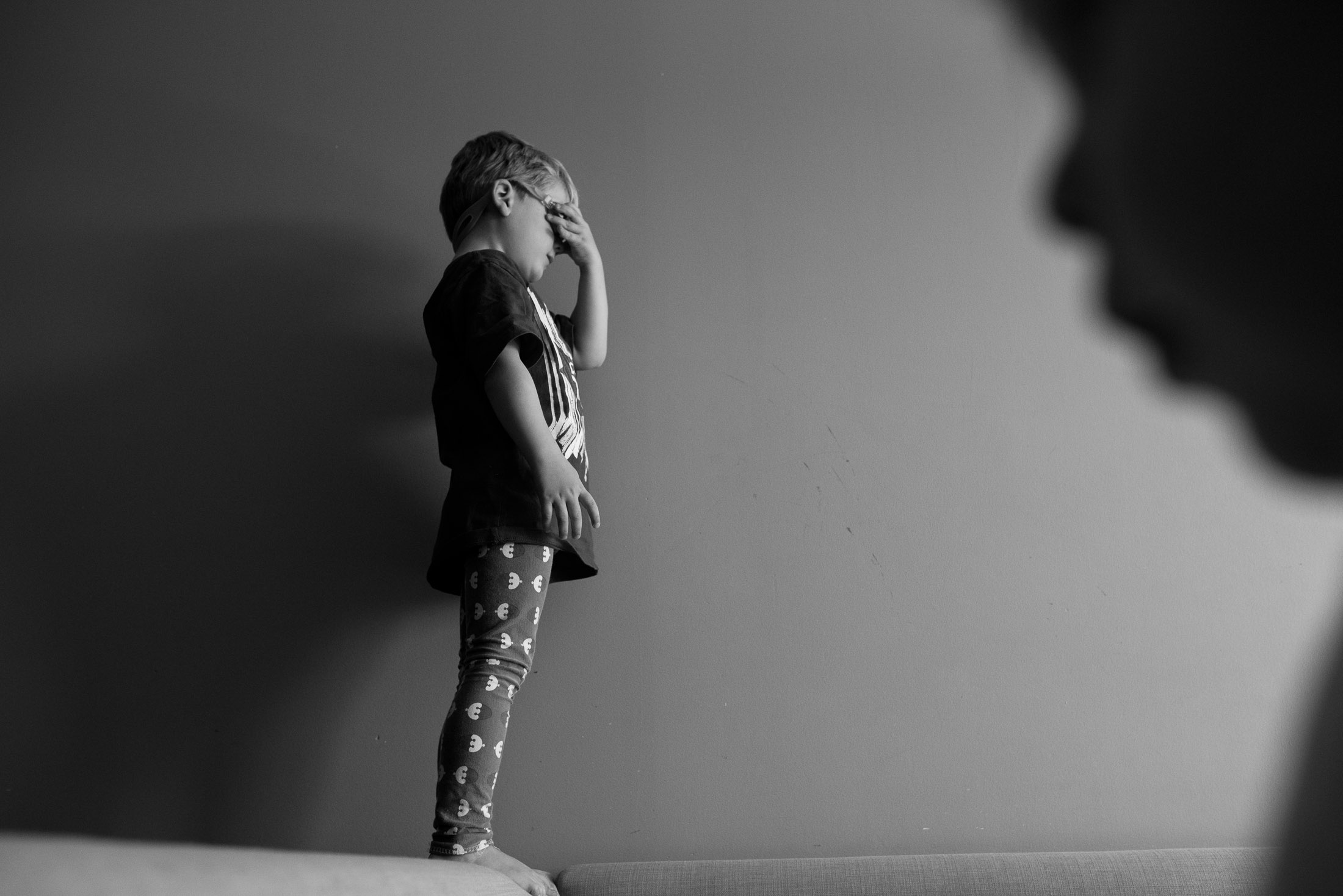 A boy is about to dive onto the couch while his brother walks into the frame. Image credit Kristine Nyborg / www.wildblueberryphotography.com