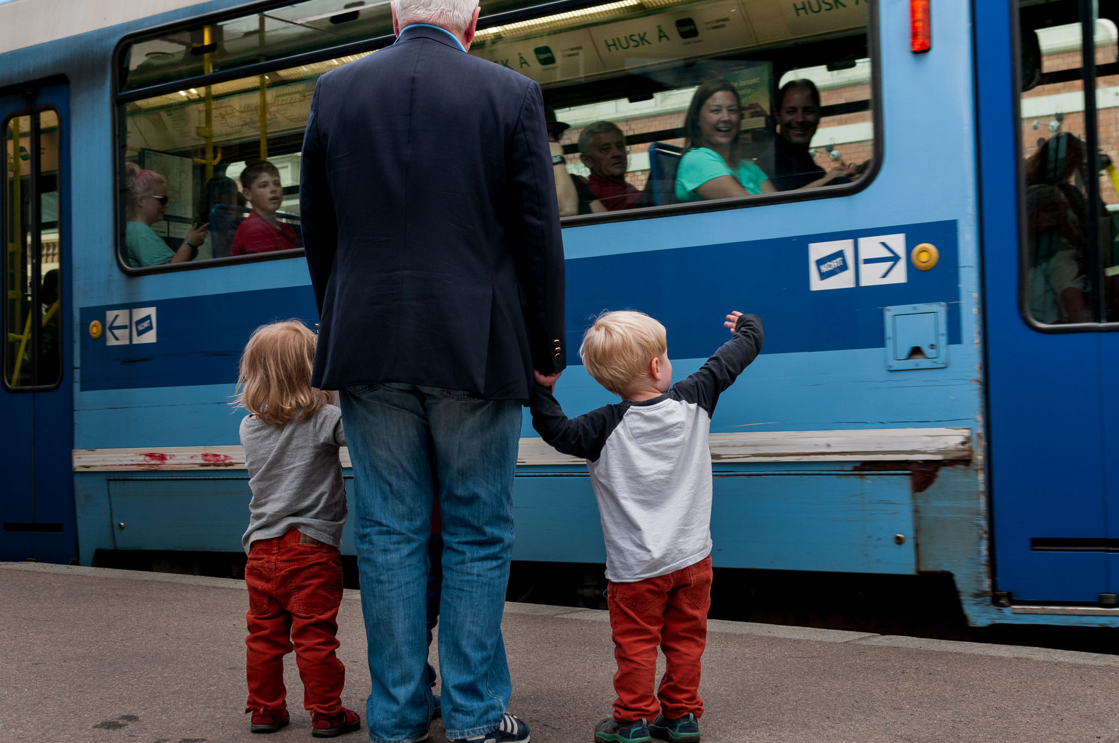 Twins wait with their grandfather as the tram passes in downtown Oslo.