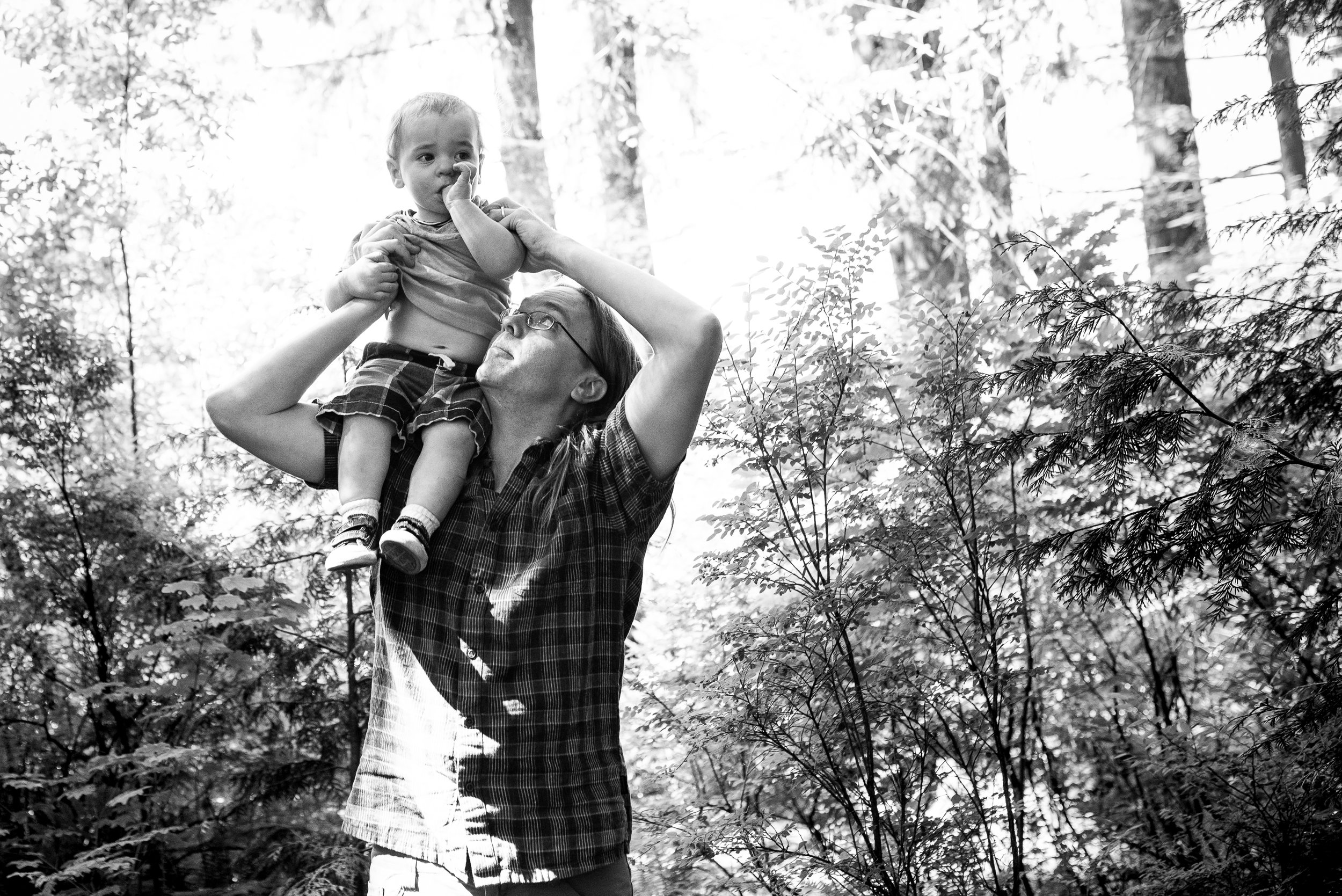 Dad carrying son on his shoulders before entering the forest in Burnaby, British Columbia.