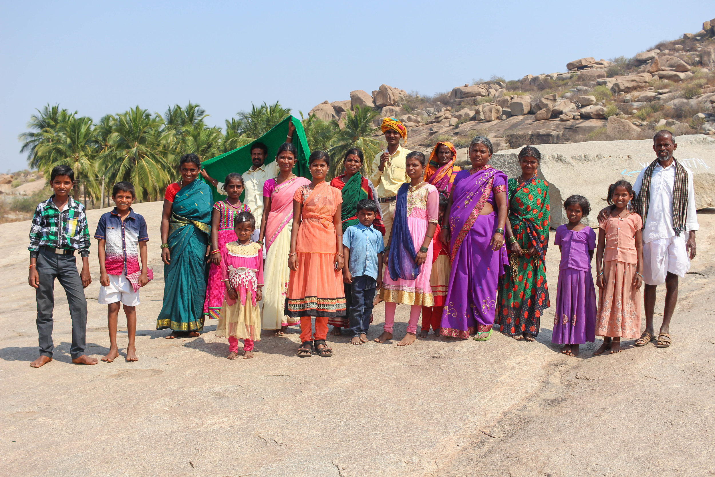 A family visiting Hampi's temples and making their way to a huge wishing tree nearby