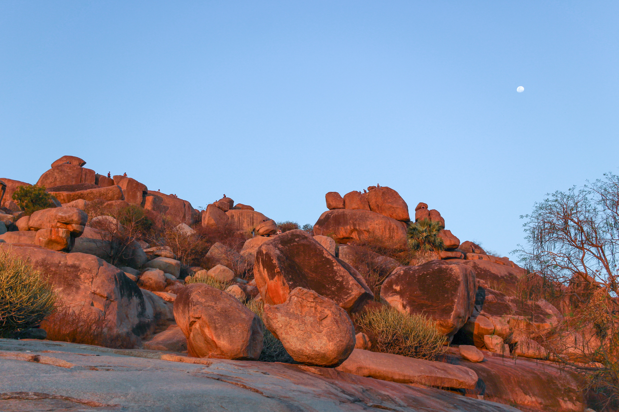 Huge golden boulders with little people on the top enjoying views at sunset