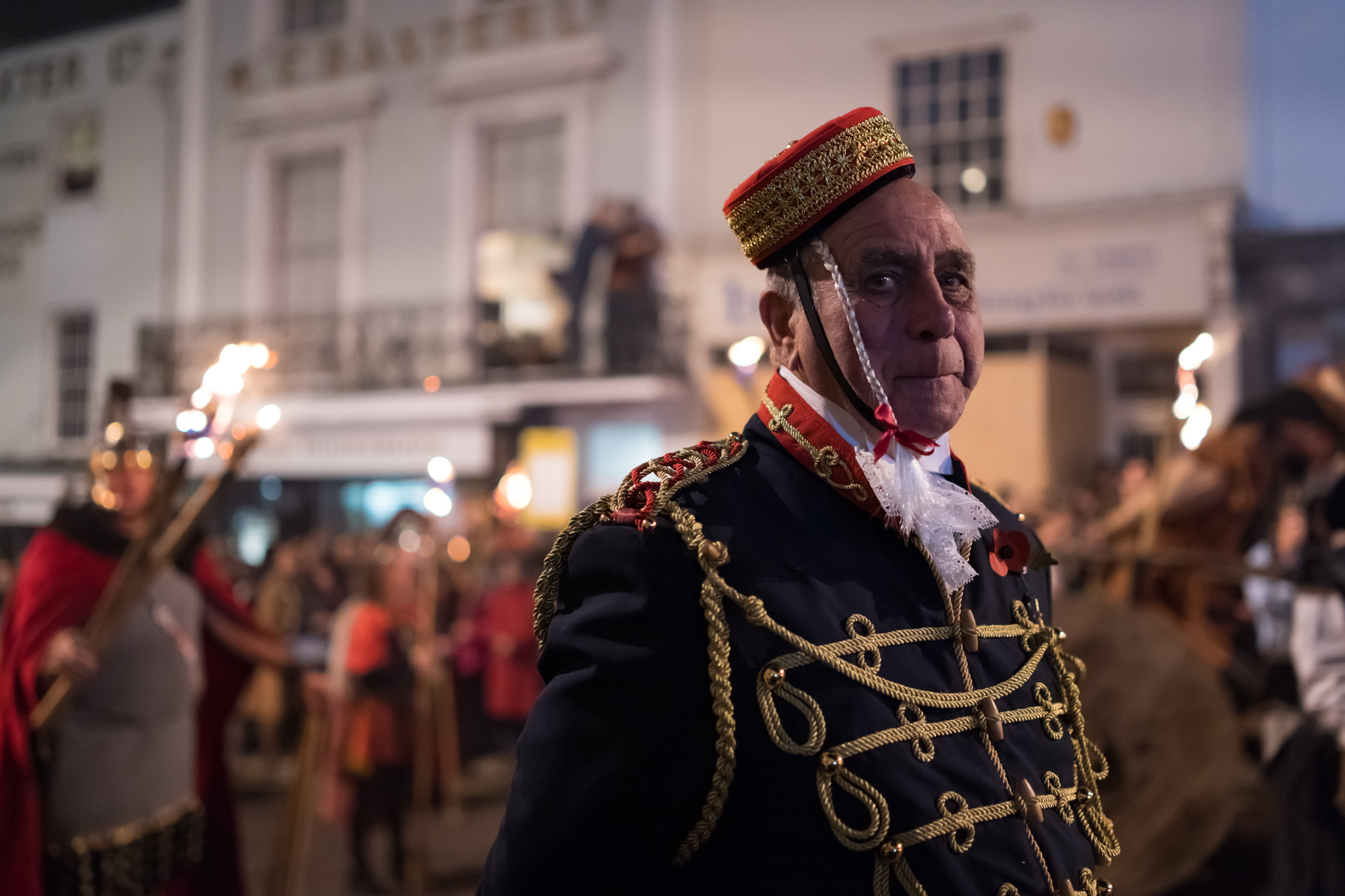 A man in one of many historical costumes worn by society members parading through the streets carrying torches, effigies and burning crosses