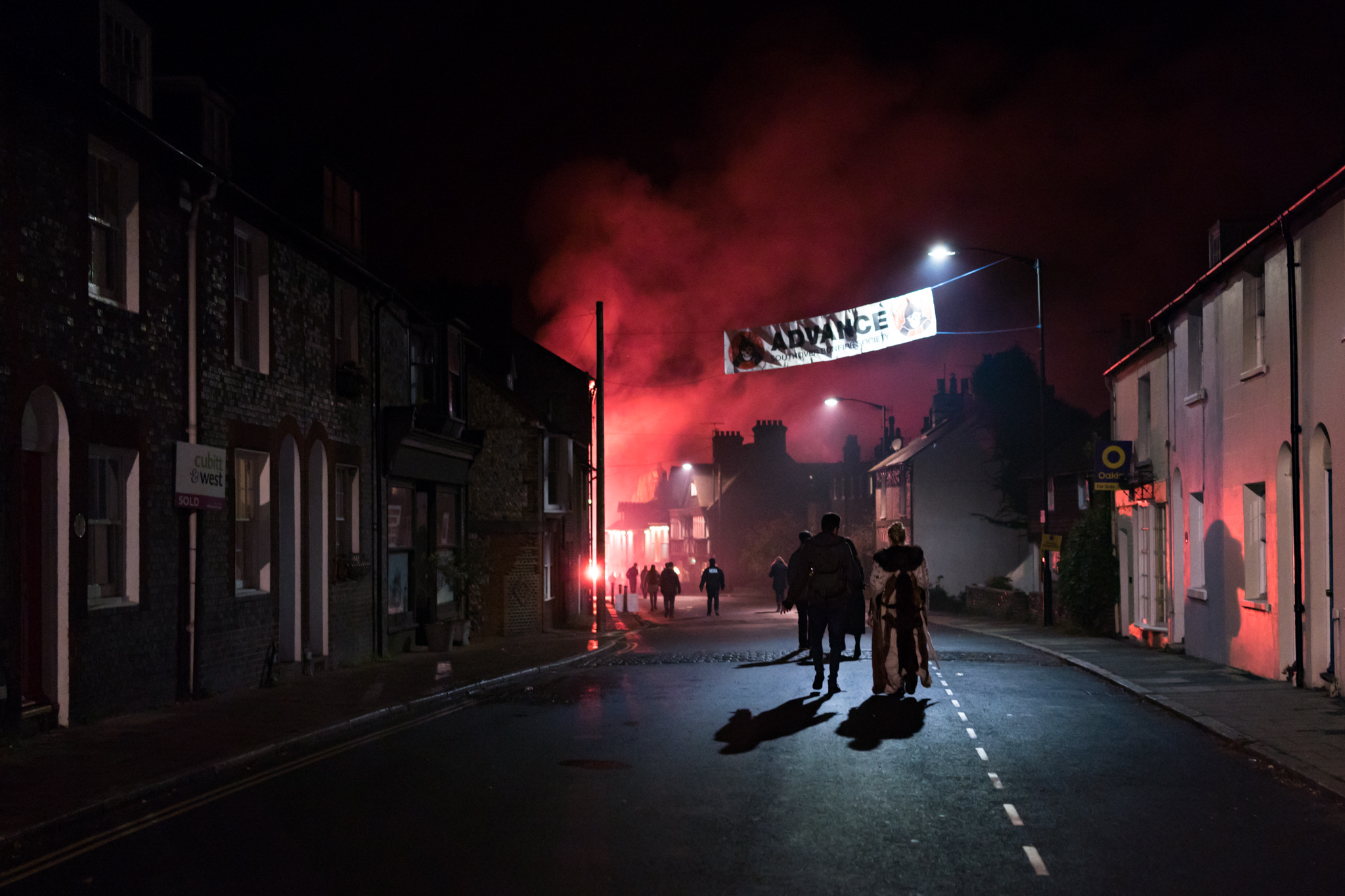 A couple walk home in the early hours of the morning as flares and firecrackers are still being lit
