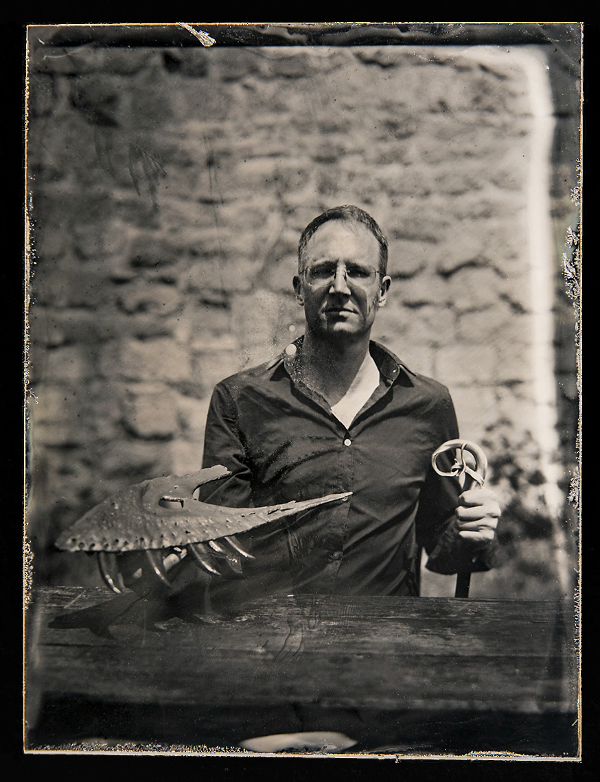 Thomas D. Carr   Wet Plate Tintype on Aluminum   Dr. Thomas Carr is an Associate Professor of Biology, at Carthage College, Director of the Carthage Institute of Paleontology, and the Senior Scientific Advisor to the Dinosaur Discovery Museum.  His research focuses on the evolution and growth of Tyrannosaurus rex and its closest relatives. The goal of Dr. Carr's  field work is to understand the changes in sedimentation, flora, and fauna during the last 1.4 million years of the Age of Dinosaurs in the American West.  The badlands of Montana provide incredible localities for discovering T. rex specimens that can help expand the research database and allow his lab to reach new insights into the biology of the King of Dinosaurs.     Dr. Carr's team is a part of the great tradition of academic fossil collecting in the American West, where every discovery is curated in a public trust for the benefit of the generations of students and scientists downstream. His lab limits explorations to public lands, as a demonstration of their commitment to the proper stewardship of vertebrate fossils for the benefit of the American (and global) public.