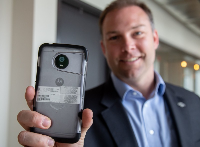 Chris Lindenau, chief revenue officer of the Decatur-based company Utility Associates, Inc., holds a Motorola phone they have adapted to work with the company's body-worn cameras system at their headquarters in Decatur Thursday, April 4, 2019. Atlanta Public Schools police officers began using the devices in March. STEVE SCHAEFER / SPECIAL TO THE AJC