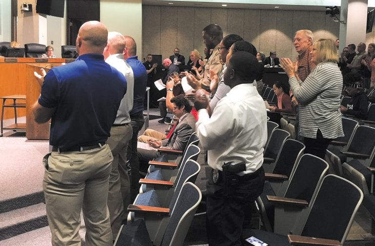 Pictured above: Police officers and the mother of three police officers, right, give a standing ovation to the County Council at the Oct. 17, 2017 meeting after the council unanimously agreed to give preliminary approval to raises for the St. Louis County Police Department approved by voters through Proposition P.    Photo by Gloria Lloyd.