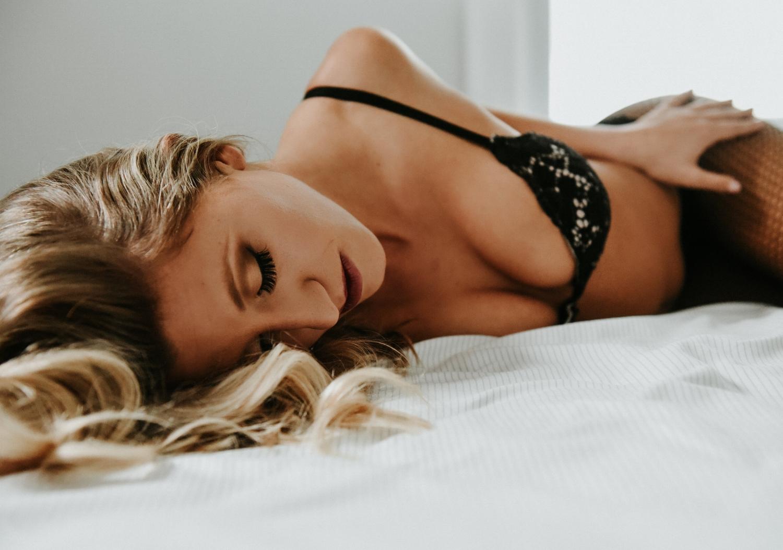 Blonde woman black bra fishnets laying on bed boudoir photography new york studio