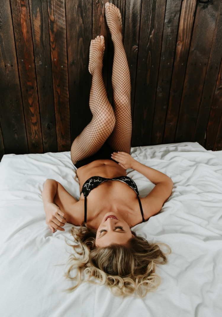 Blonde woman in black lace lingerie fishnets laying wood bedframe boudoir photography new york studio